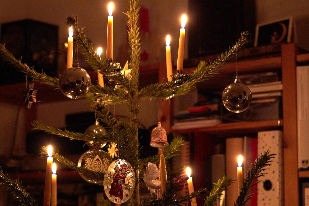 Christbaumkugeln bei Kerzenschein am Weihnachtsbaum.